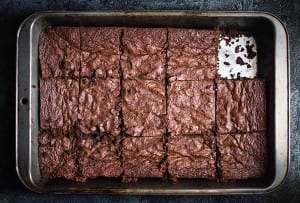 A metal baking pan of gluten free brownies with one piece missing