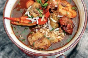 A two-handle bowl of seafood gumbo on a piece of wood.