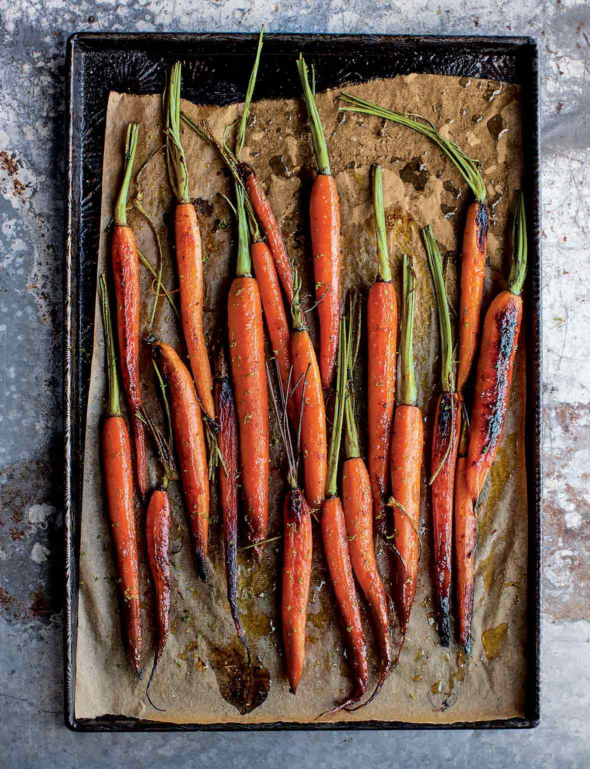 A bunch of roasted sweet and spicy carrots on a parchment-lined baking sheet.