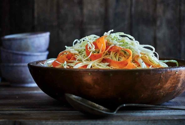 A wooden bowl filled with South Carolina slaw with a spoon beside it.