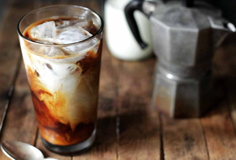 A glass of cold brew coffee with a French press and jar of cream in the background.