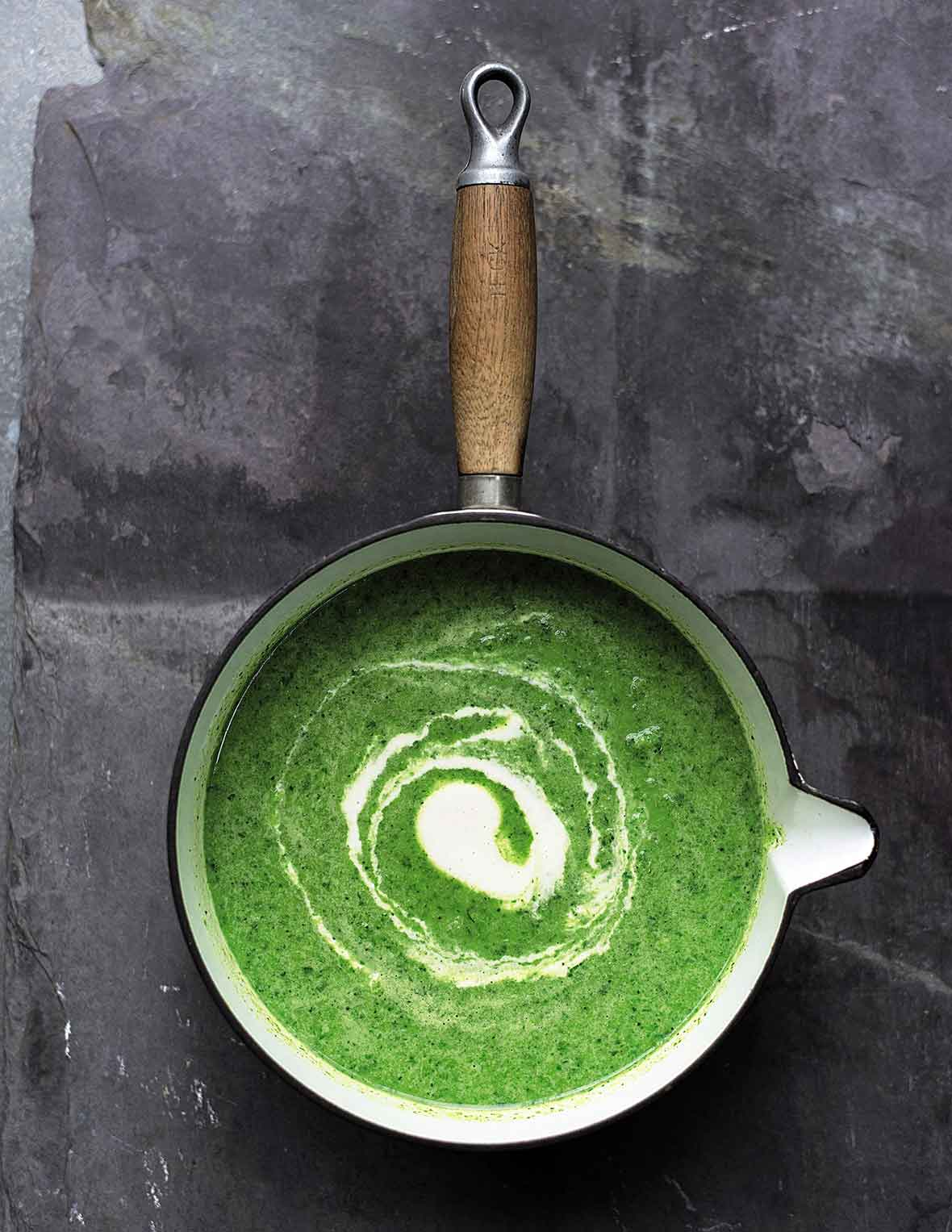 A saucepan filled with green soup, with a swirl of cashew cream in the center.