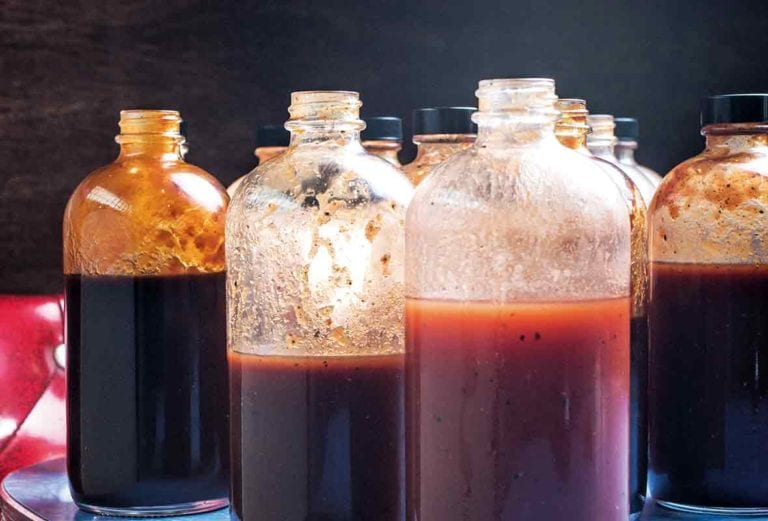 Several open glass bottles of barbecue sauces, including a vinegar barbecue sauce.