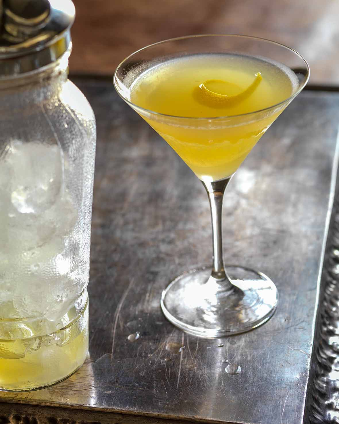 Martini glass filled with yellow Bee's Knees cocktail--honey, gin, and lemon--with a lemon twist, a shaker on the side
