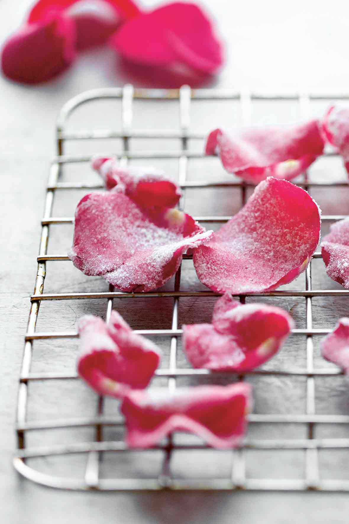 Several candied rose petals on a wire rack.