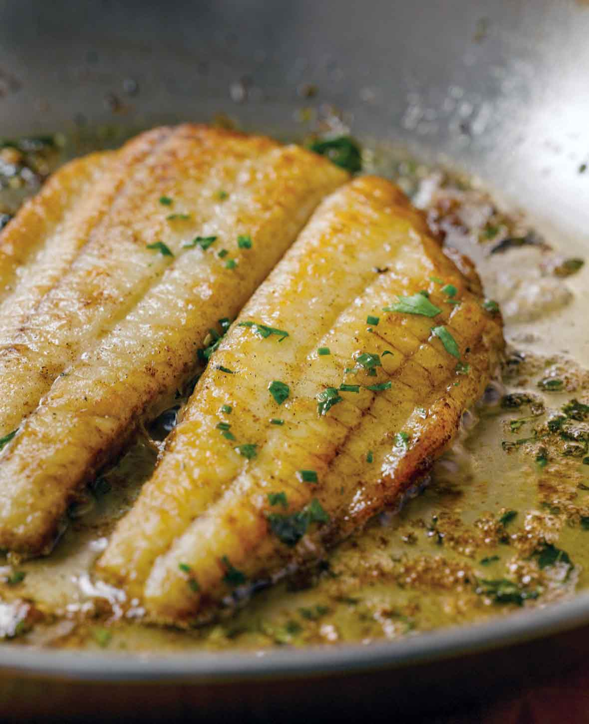 Two fillets of flounder in a lemon butter sauce in a skillet topped with chopped parsley