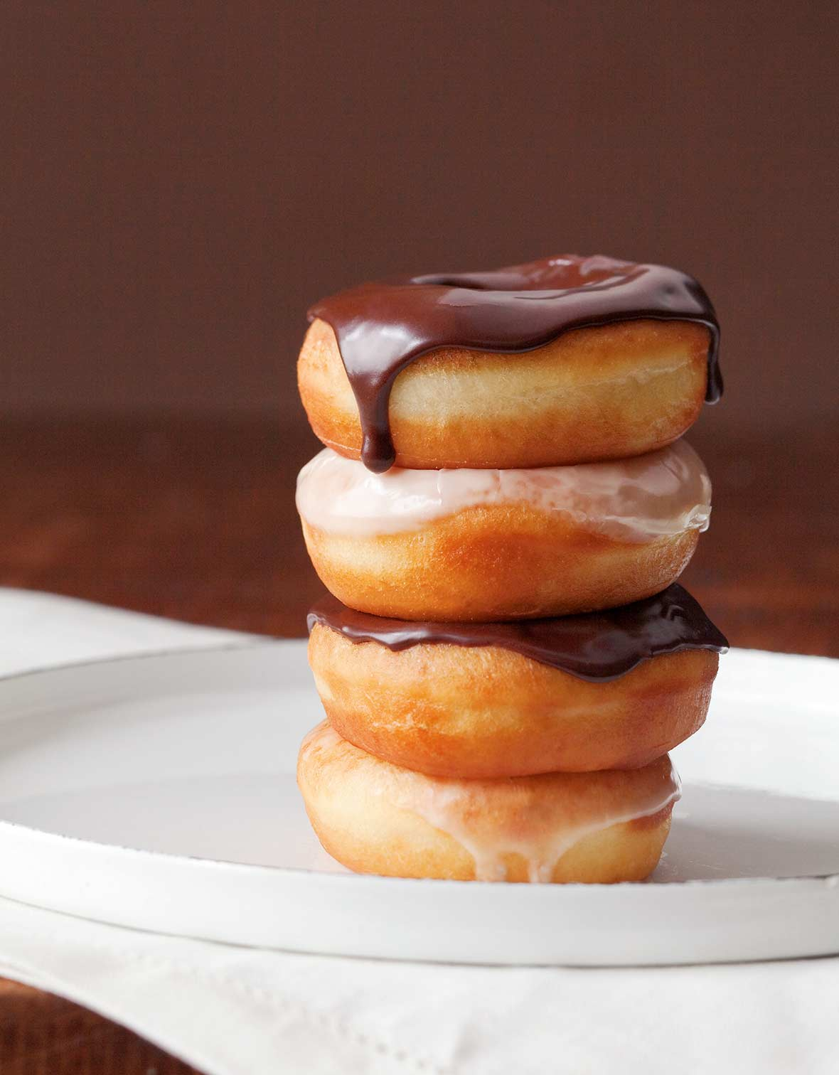 Four glazed doughnuts stacked on top of each other, two with chocolate glaze, 2 with vanilla glaze