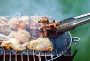 Pieces of grilled chicken with balsamic vinaigrette cooking on a grill, being turned with a pair of tongs.