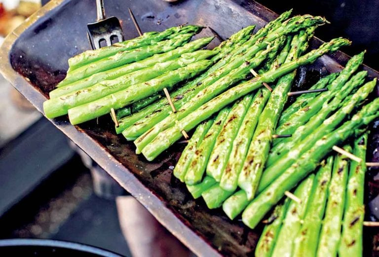 A cook demonstrating how to grill asparagus with several rafts of asparagus spears connected with wooden skewers.