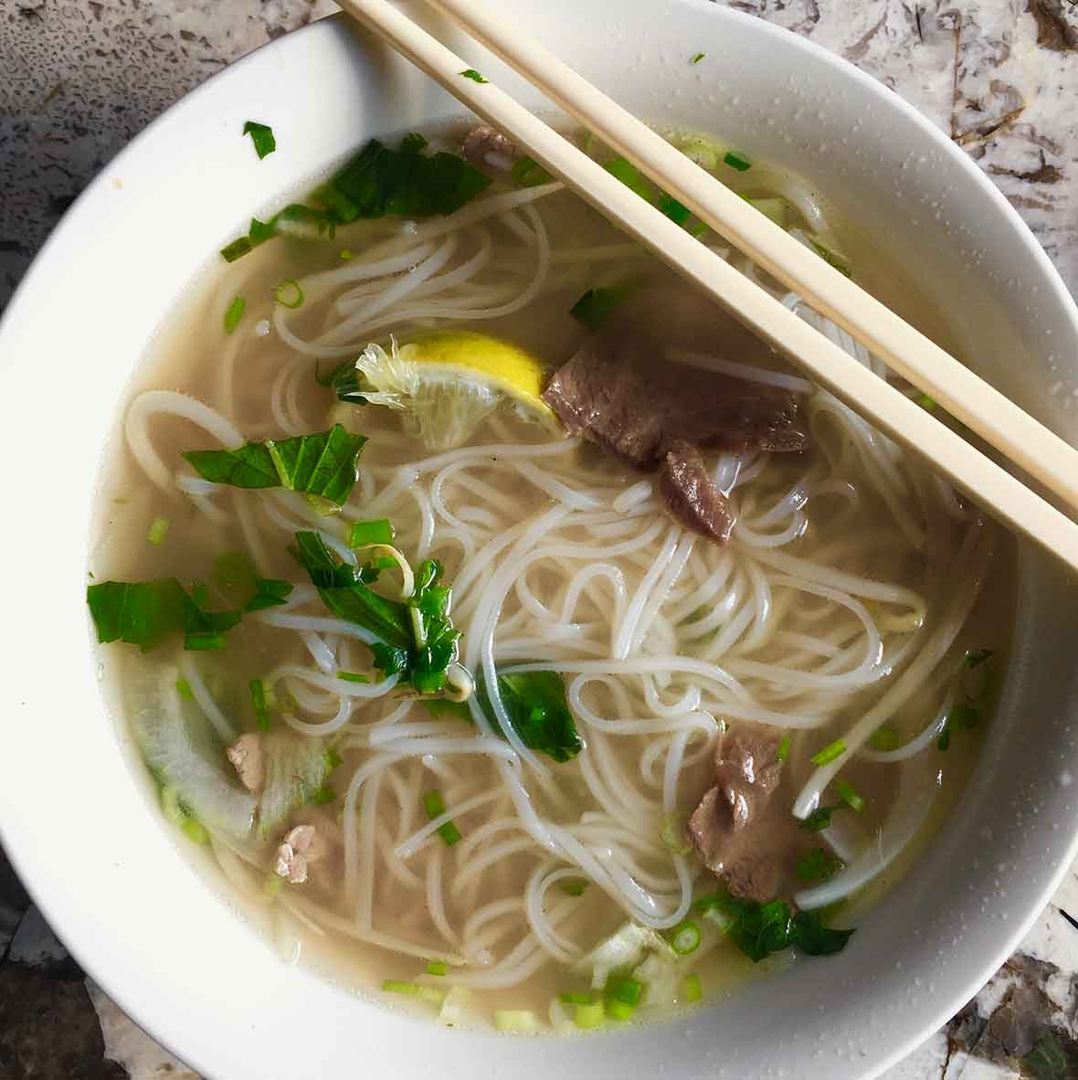 A bowl of authentic Vietnamese pho with rice noodles, beef, lemon, basil, and scallions in it and a pair of chopsticks resting on top of the bowl.