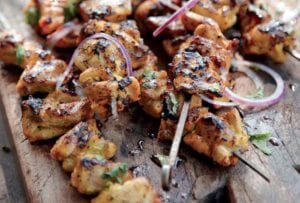 Seven grilled chicken skewers with red onion, coconut milk, and cilantro on a wooden board