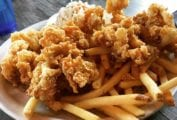 A paper basket filled with golden fried clams and fries