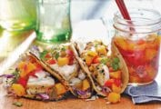 An open jar of peach salsa next to three fish tacos topped with peach salsa.