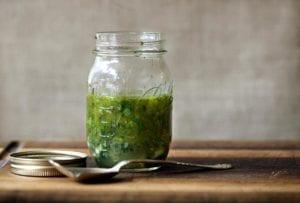 Mason jar of Greek marinade with parsley, oregano, thyme, rosemary, basil on a cutting board