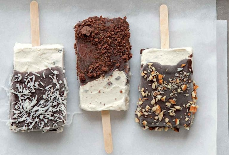 Three homemade ice cream bars, coated with chocolate and sprinkled with almonds, coconut, and chocolate crumbs.