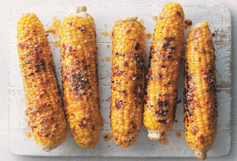 Five ears of Mexican corn on the cob on a white wooden board.