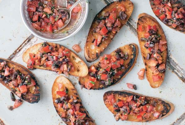Eight slices of tomato bruschetta with a bowl of bruschetta topping on the side.