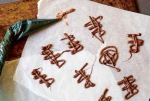 Squiggles of melted chocolate on a piece of parchment with a piping bag lying beside.