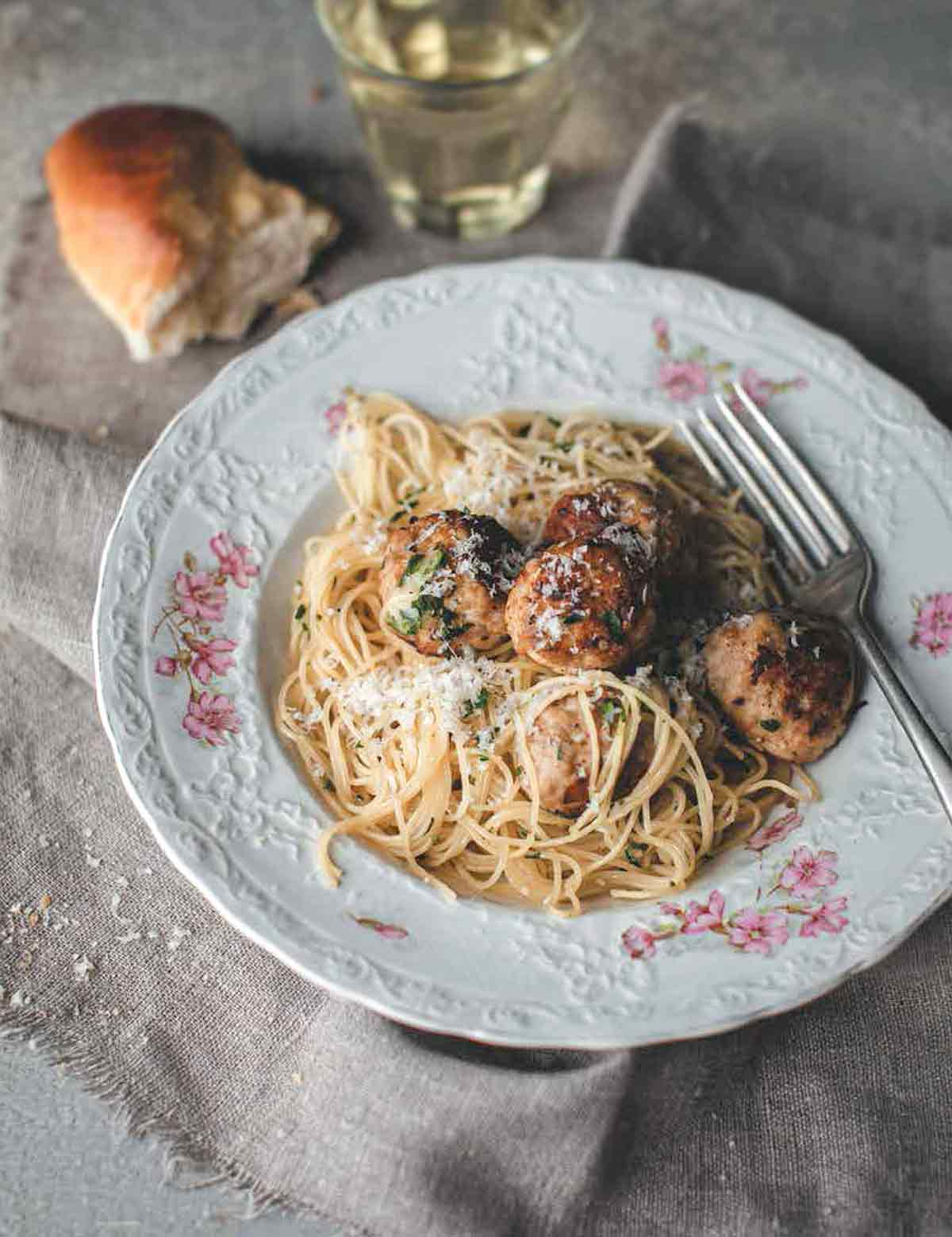 A patterned bowl filled with turkey meatballs with angel hair pasta, and a piece of bread and glass of white wine next to the bowl.