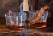 Two glasses of bacon bourbon with strips of cooked bacon in each glass and a bottle of bourbon in the background.