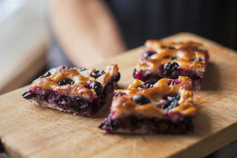 Three pieces of grape focaccia on a wooden board.