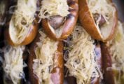 A stack of grilled beer braised bratwurst covered in sauerkraut.
