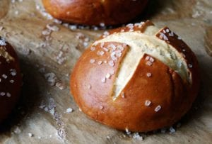 Three pretzel rolls on a piece of parchment.