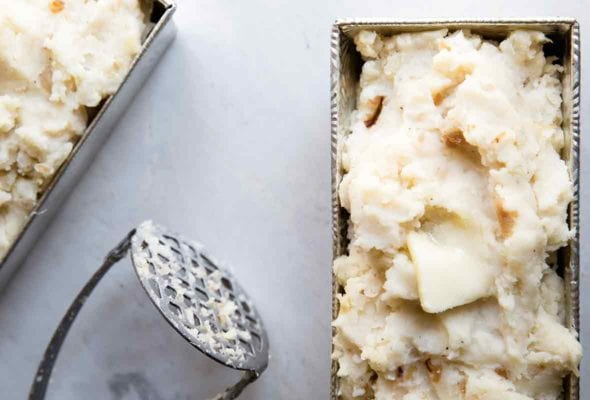 Two metal loaf pans filled with roasted garlic mashed potatoes with a masher resting in between them.