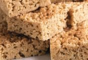 Several squares of pumpkin spice rice krispie treats stacked on a brown and white plate.