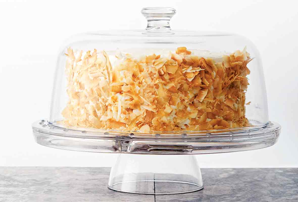 A coconut carrot cake with cream cheese frosting and toasted coconut on the sides on a glass cake platter with a glass domed lid.