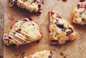 Five cranberry scones with two drizzled with white chocolate glaze on a parchment-lined rimmed baking sheet.