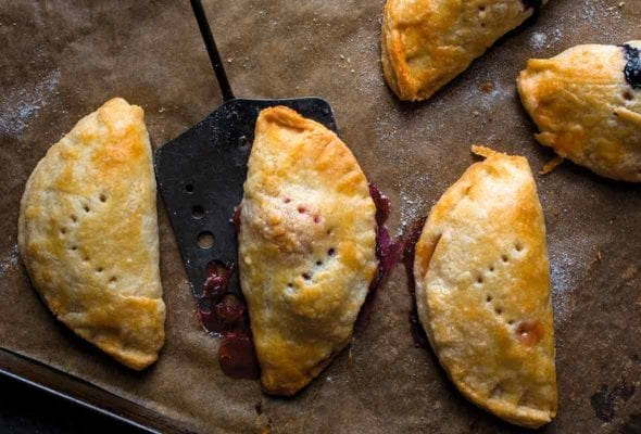 Five hand pies on a parchment-lined baking sheet with a spatula lifting one off.