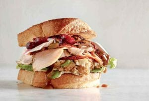 A leftover turkey cranberry sandwich on a white surface.