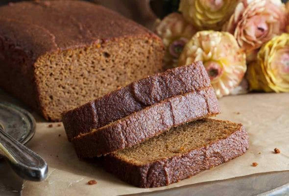 A loaf of paleo pumpkin bread with three slices cut off the end.