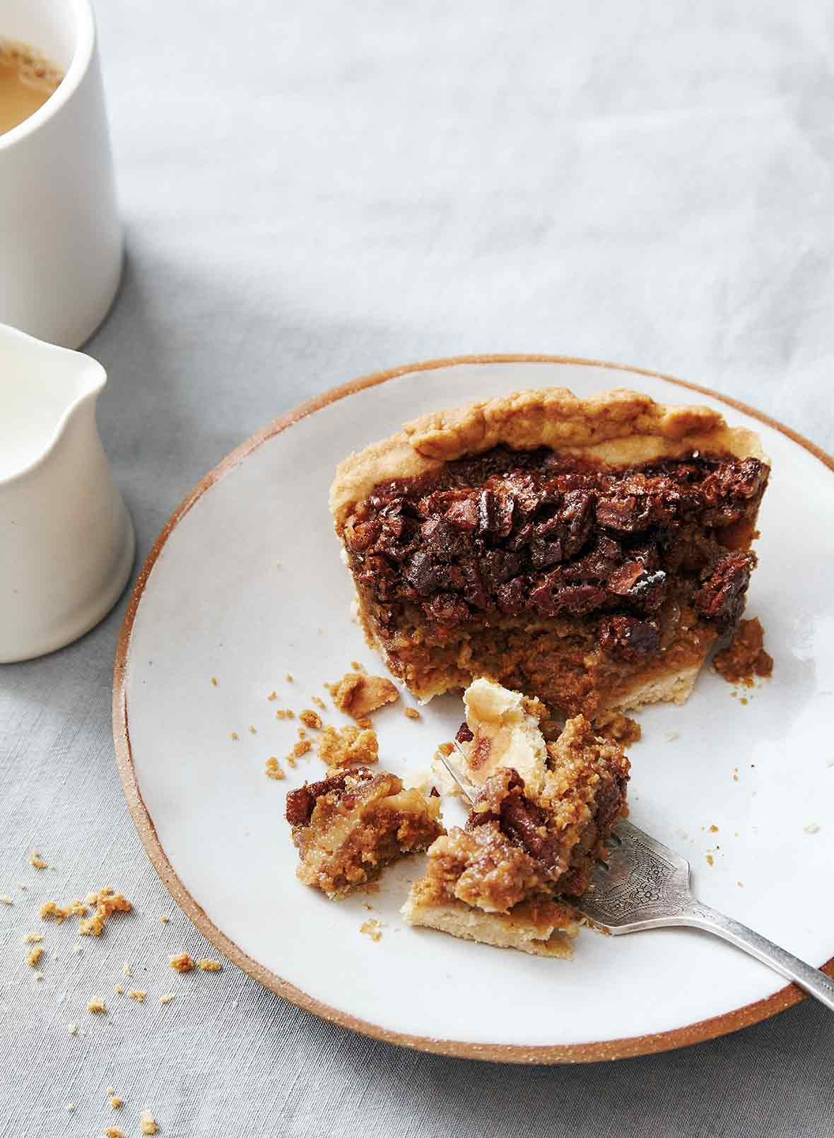 A slice of half-eaten pumpkin pecan pie on a gold rimmed plate