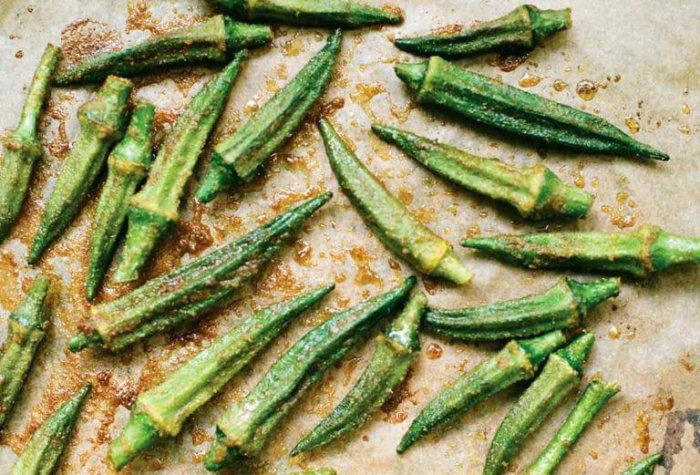 Pieces of roasted okra with spices on a parchment-lined baking sheet.