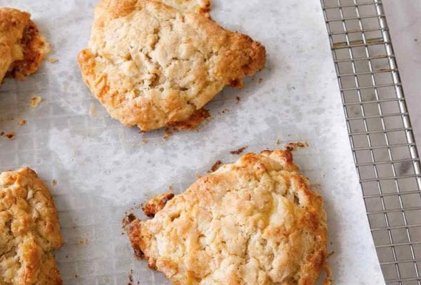 Six apple and white cheddar scones on a piece of parchment on top of a cooling rack.