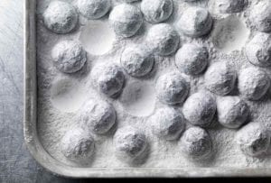 A rimmed sheet pan filled with truffles coated in confectioners' sugar