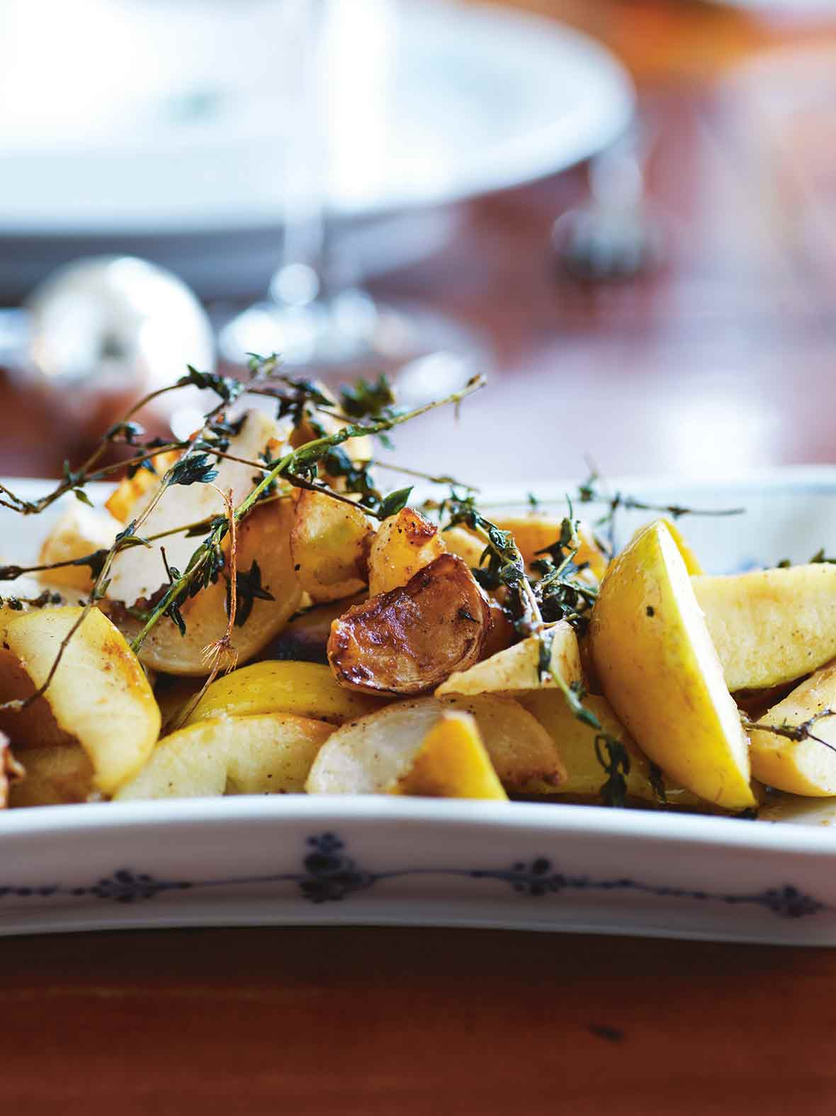 A white platter filled with turnip and apples segments, topped with thyme sprigs