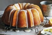 A lemon pound cake resting on a round wire rack, drizzled with a white icing glaze