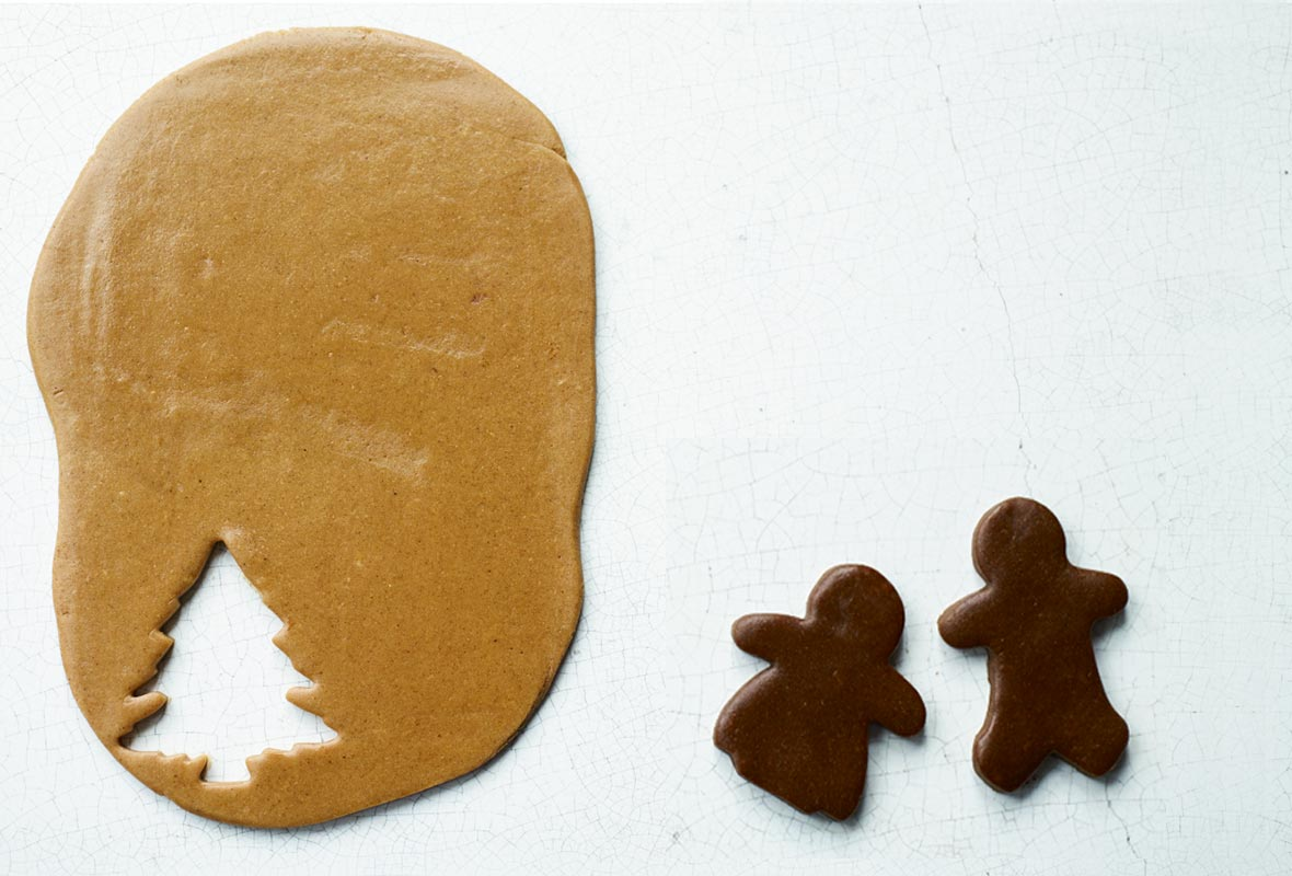 Pieces of light and dark gingerbread, with two people cut out of the dark, and a tree shape cut out of the light gingerbread.
