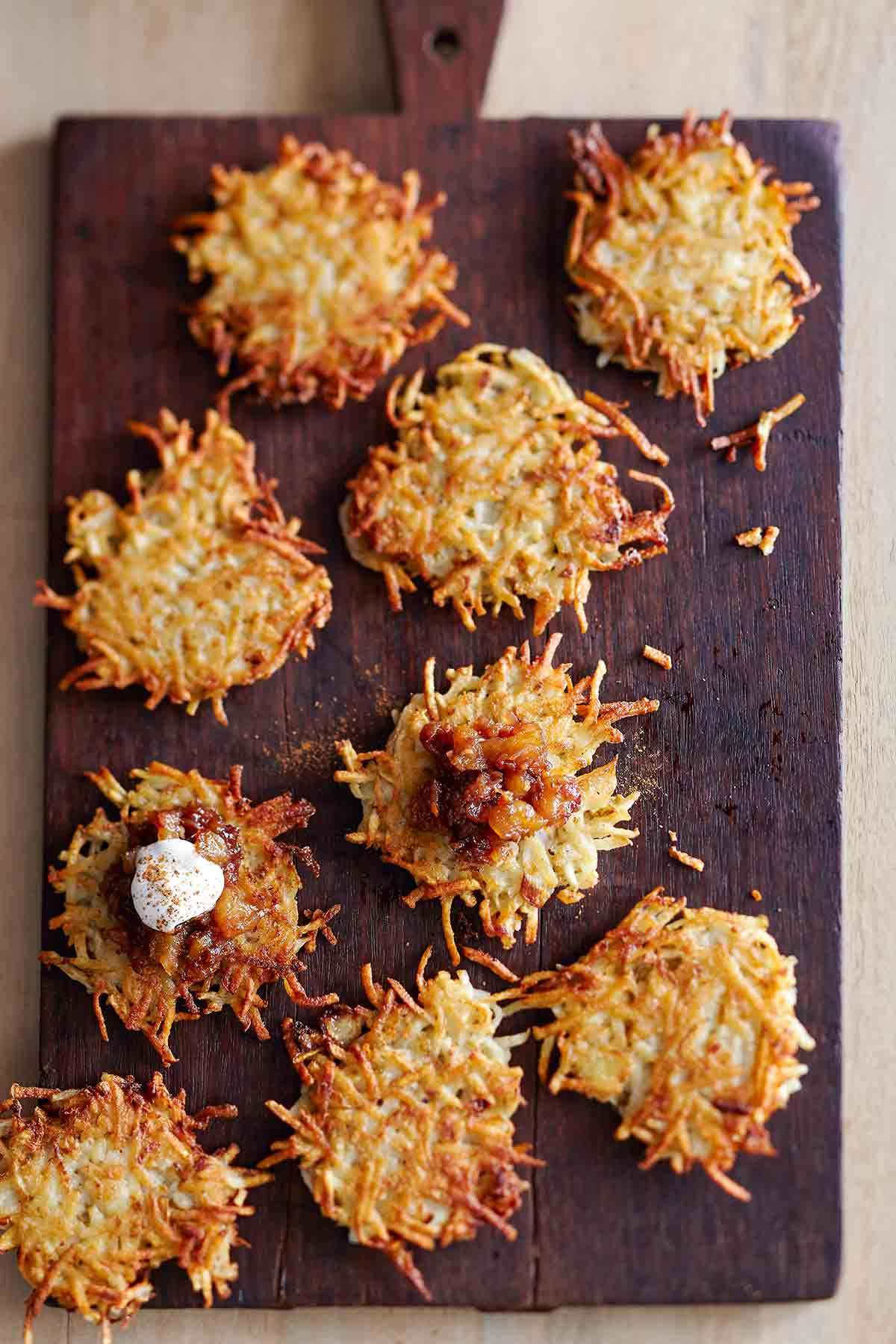 Nine potato latkes with apple-date chutney and cinnamon sour cream on a wooden cutting board.