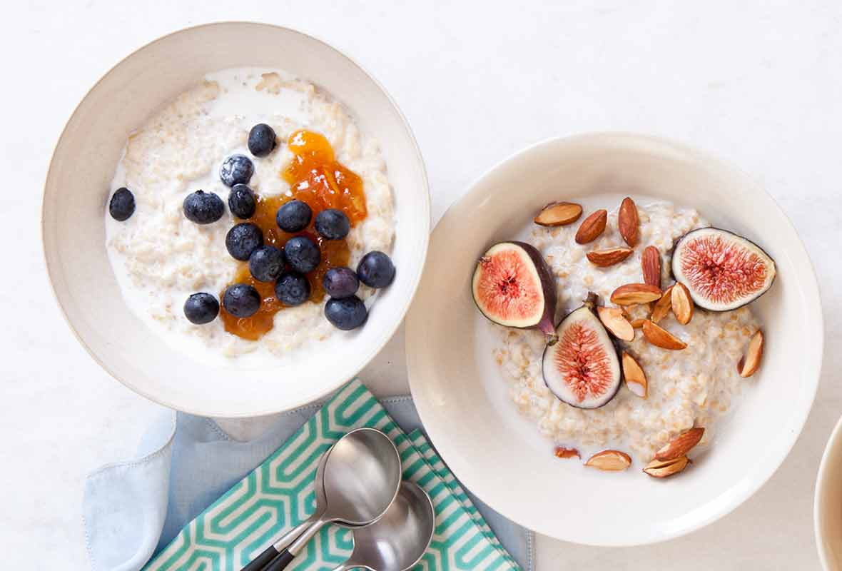 Two white bowls filled with porridge; one topped with blueberries and the other with figs and almonds