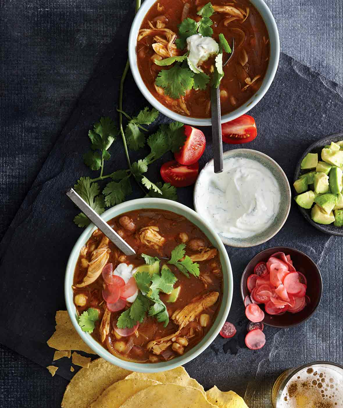 Two bowls of chicken posole, with a bowl of sour cream, some tomato wedges, cilantro, sliced radish, and tortilla shells scattered around them.