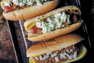 One chili bun and two slaw dogs on a rimmed baking sheet.