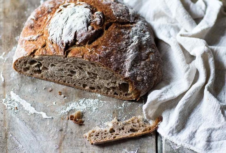 A loaf of Galician rye bread with a slice cut off to show the airy texture.