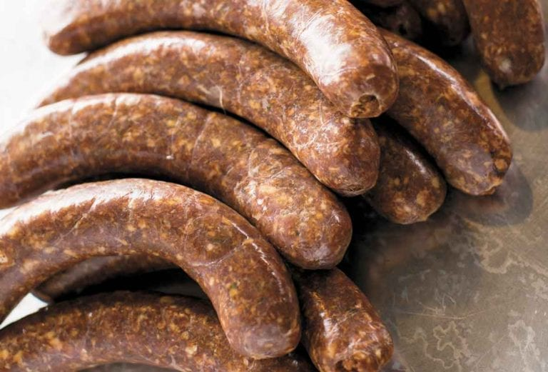 Several links of homemade chorizo on a metal surface.