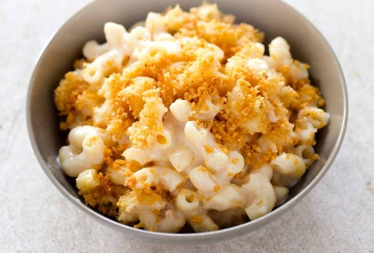 A grey bowl filled with baked mac and cheese topped with bread crumbs.