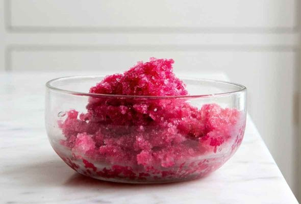 A glass bowl filled with Campari sorbet on a white marble countertop.