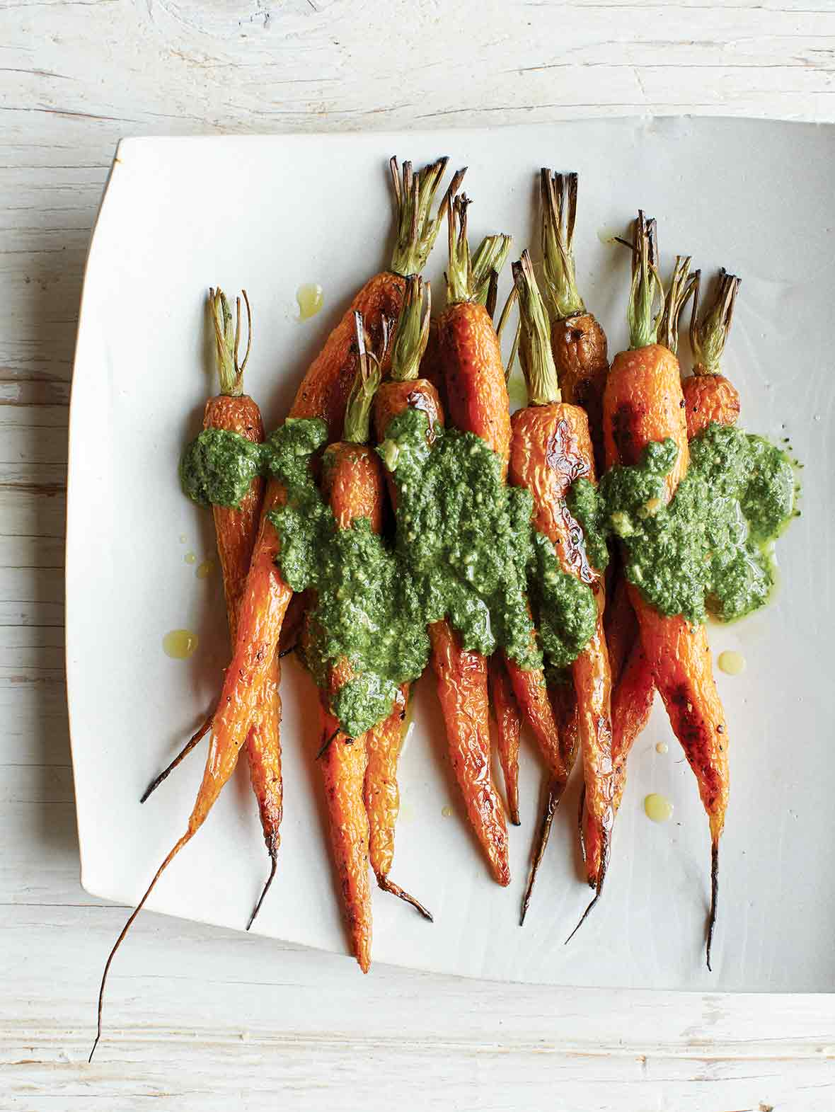 A white platter with nine roasted carrots covered in carrot top pesto.